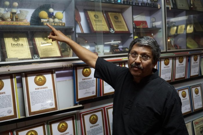 Dr S Ramesh Babu, a retired metallurgical scientist and world record holder poses in his home points to shuttle cocks used in record-breaking attempt. DH Photo