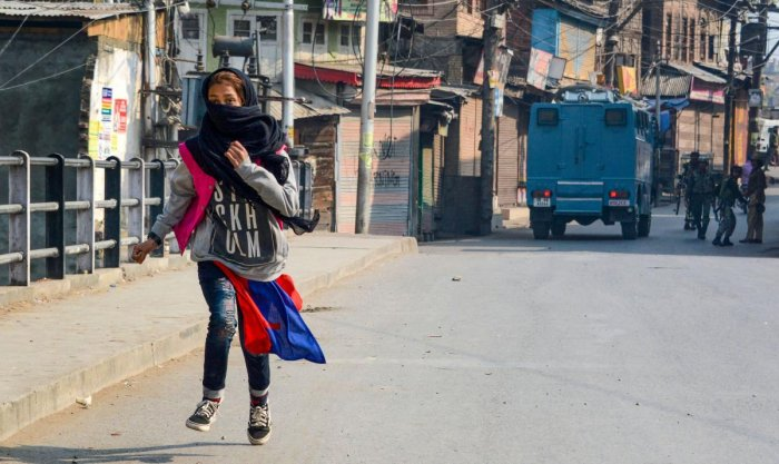 A girl runs for cover after throwing stones during a protest in Srinagar. (PTI Photo)