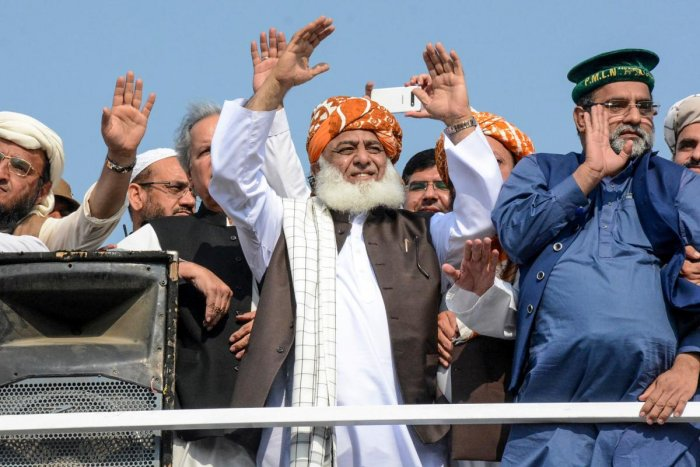 "Chief of the Jamiat Ulema-e-Islam party Maulana Fazlur Rehman (C) gestures to supporters on his arrival during an anti-government ""Azadi March"" march towards Islamabad. (AFP Photo)"