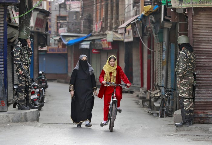 A Kashmiri girl rides her cycle past security force personnel standing guard in front of closed shops in a street in Srinagar on October 30, 2019. Reuters