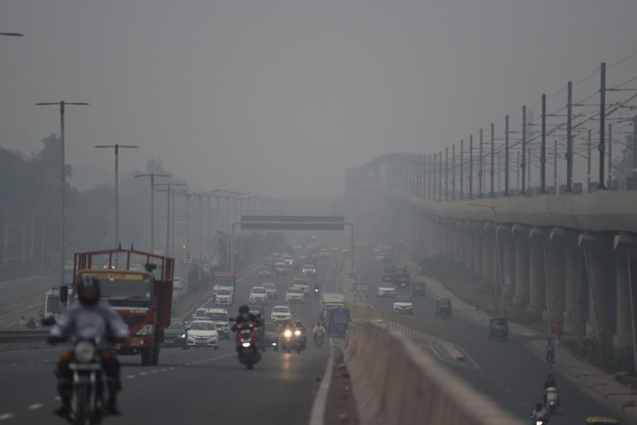 Commuters drive along a road under heavy smog conditions in Faridabad. (AFP Photo)