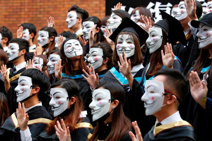 University students wearing Guy Fawkes masks pose for a photoshoot of a graduation ceremony to support anti-government protests at the Hong Kong Polytechnic University, in Hong Kong (Reuters Photo)