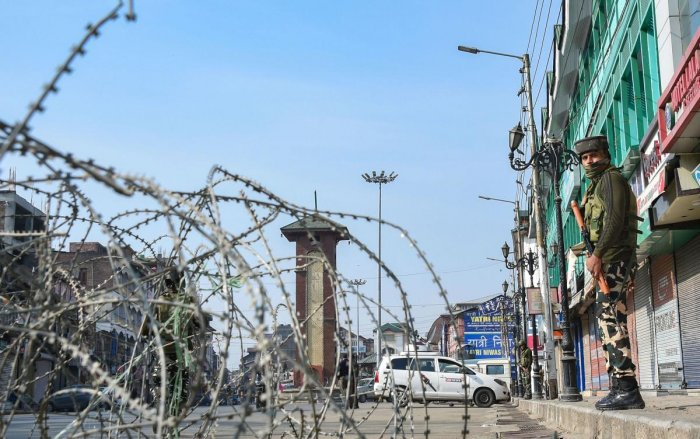A security jawan keeps vigil as a road is blocked with barbed wires at Lal Chowk after bifurcation of the Jammu and Kashmir state came into existence. (PTI Photo)