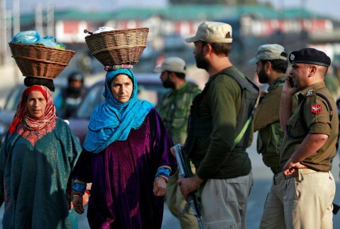 Kashmiri women walk past Indian policemen standing guard in a street in Srinagar October 31, 2019. (REUTERS)