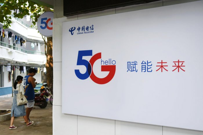 People holding their mobile phones walk past a China Telecom 5G sign at a university in Haikou, Hainan province, China. Reuters file photo