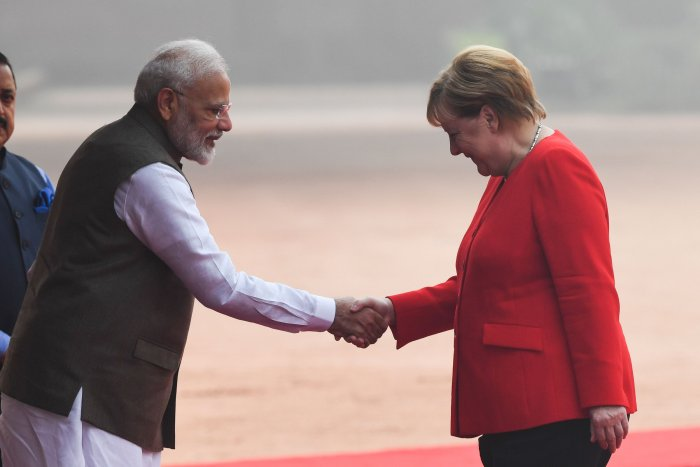 India's Prime Minister Narendra Modi (L) shakes hands with German Chancellor Angela Merkel during a welcoming ceremony at Rashtrapati Bhavan. (AFP Photo)