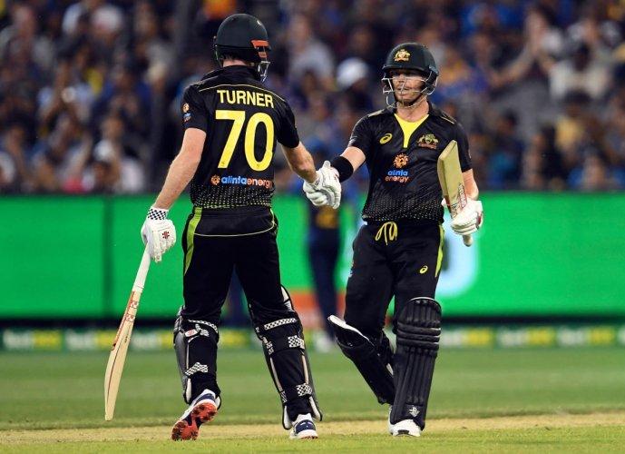 Australia's David Warner celebrates scoring 50 runs against Sri Lanka with teammate Ashton Turner (L) during their Twenty20 cricket match played in Melbourne on November 1, 2019. (Photo by WILLIAM WEST / AFP)