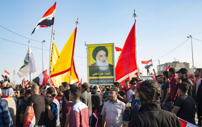 Iraqi demonstrators carry flags and an image of Shiite cleric Ayatollah Ali Husaini al-Sistani, during ongoing anti-government protests. (Photo AFP)