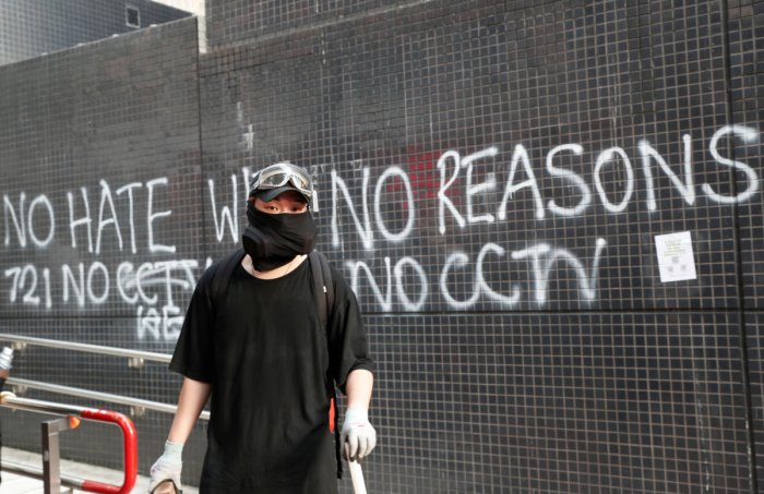 """A protester stands in front of a graffiti during a march billed as a global """"emergency call"""" for autonomy, in Hong Kong, China November 2, 2019. Reuters"""