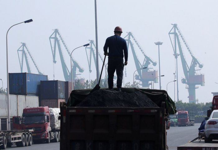 A labourer loads coal in a truck next to containers outside a logistics center. (Reuters Photo)
