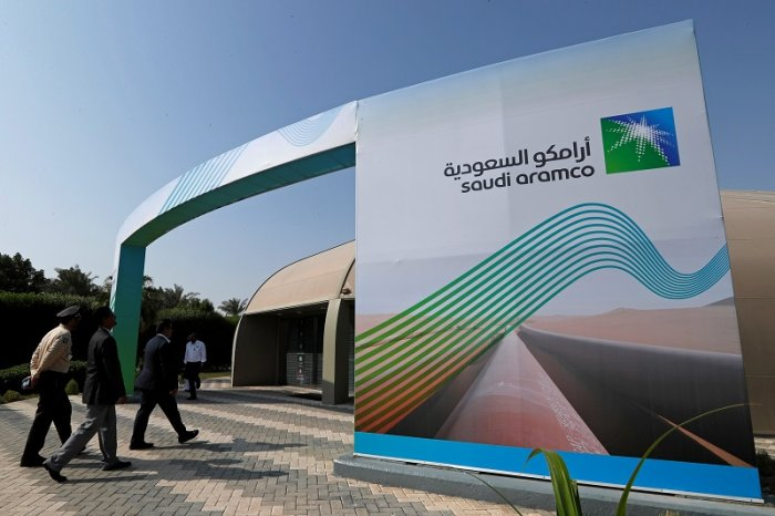 The logo of Aramco is seen as security personnel walk before the start of a press conference by Aramco at the Plaza Conference Center in Dhahran, Saudi Arabia. (Reuters Photo)