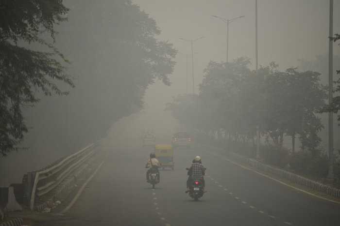 Motorists drive along a road under heavy smog condition in New Delhi. (AFP Photo)