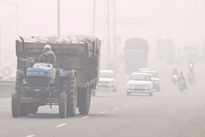 Vehicles ply on NH-2 amid thick smog, in Mathura. (PTI Photo)