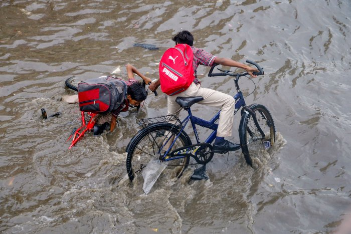 A cyclist loses his balance in a flooded street during rainfall, in Ajmer. (PTI Photo)