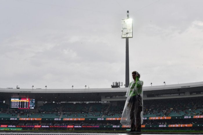 A volunteer is seen as the Twenty20 cricket match between Australia and Pakistan is halted due to rain at the Sydney Cricket Ground in Sydney. AFP