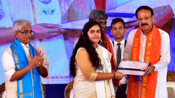 A student receives gold medal from Vice President Venkaiah Naidu at the 17th annual convocation at NITK, Surathkal, on Saturday. DH Photo