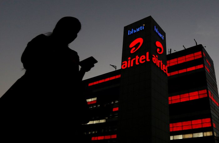 A girl checks her mobile phone as she walks past the Bharti Airtel office building in Gurugram, previously known as Gurgaon, on the outskirts of New Delhi. (Reuters Photo)