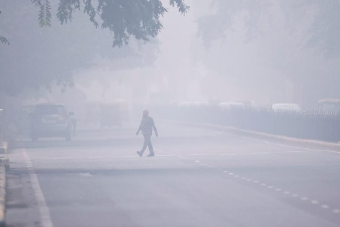 A man crosses a street in smoggy conditions in New Delhi. AFP