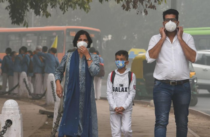 People wear masks amid heavy smog as the air quality further dipped in New Delhi on Sunday. PTI