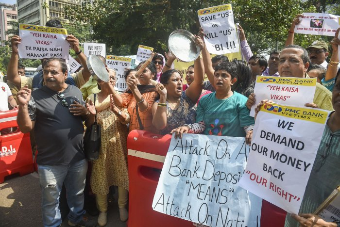 PMC Bank account holders hold placards and raise slogans as they protest outside RBI office, at BKC in Mumbai. (PTI Photo)
