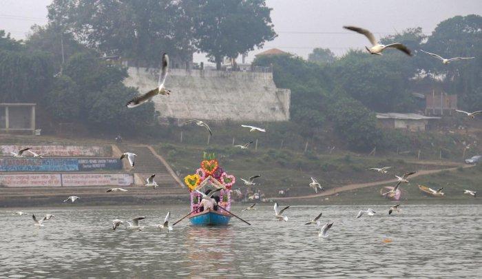 Birds fly over Narmada river as a boat ferries across, in Jabalpur, Sunday, Nov. 03, 2019. (PTI Photo)