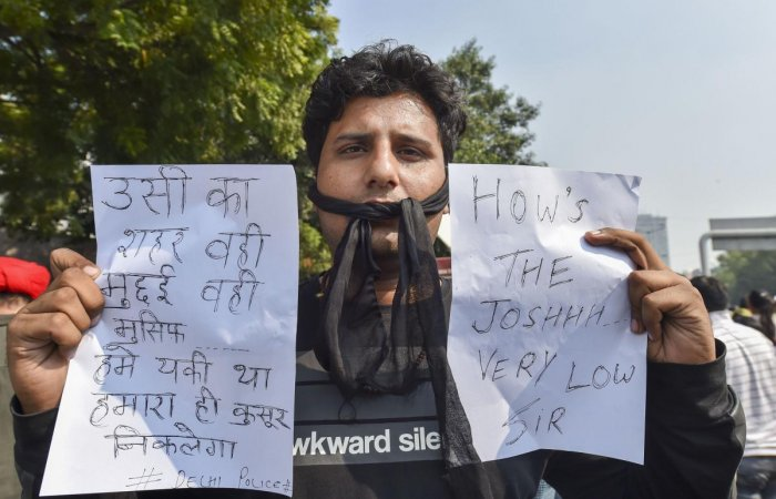 A Delhi Police man displays messages during a protest against the alleged repeated incidents of alleged violence against them by lawyers, at the PHQ in New Delhi on Tuesday. (PTI Photo)