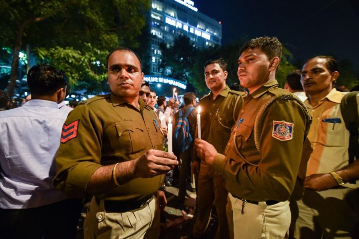 Delhi Police personnel hold a candle light protest at Delhi Police Headquarters over alleged repeated incidents of violence against them by lawyers, in New Delhi. (PTI Photo)