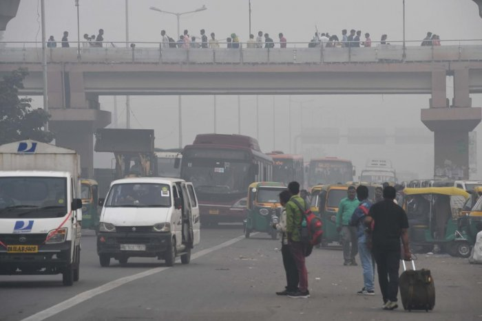 People make their way on a street in smoggy conditions in New Delhi. (AFP Photo)