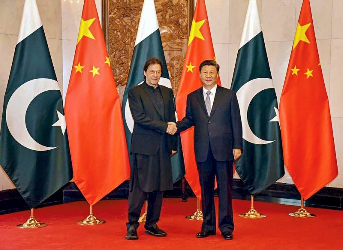 Chinese President Xi Jinping shakes hands with Pakistani Prime Minister Imran Khan, in Beijing. (AFP Photo)