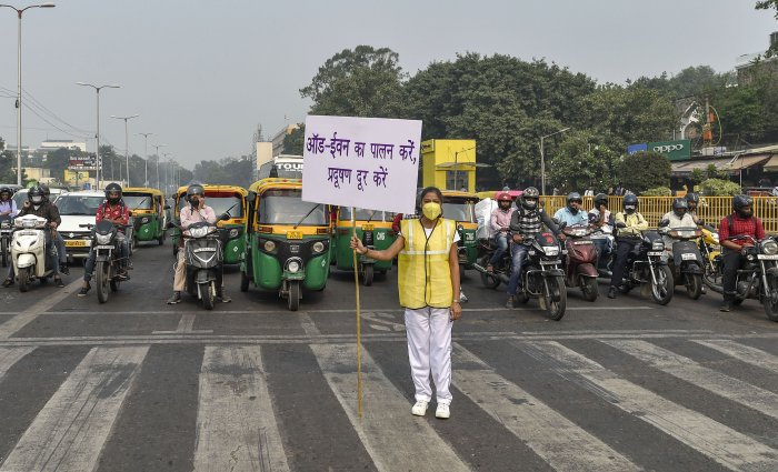 A Civil Defence volunteer displays a placard asking people to obey the odd-even rule, at ITO in New Delhi. (PTI Photo)