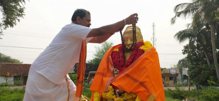 Hindu Makkal Katchi leader Arjun Sampath adoring Thiruvalluvar statue with rudraksha mala in Thanjavur on Wednesday. (DH Photo)