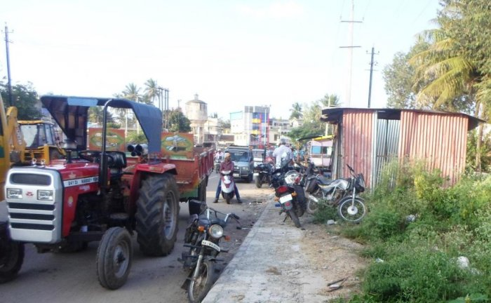 Petty shops and parked vehicles on the footpath on Ajjampura-Birur Road.