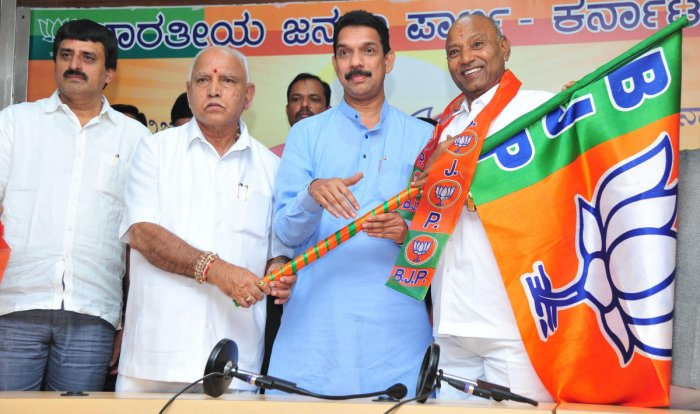 State BJP president hands over BJP flag to Vijayshankar at the party office in Bengaluru on Tuesday. DH Photo