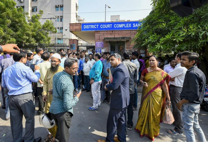 People wait outside Saket courts during lawyers protest inside the court premises over last week's incident of clashes between lawyers and police at Tis Hazari Court complex, in New Delhi, Wednesday, Nov. 6, 2019. (PTI Photo/Kamal Singh)