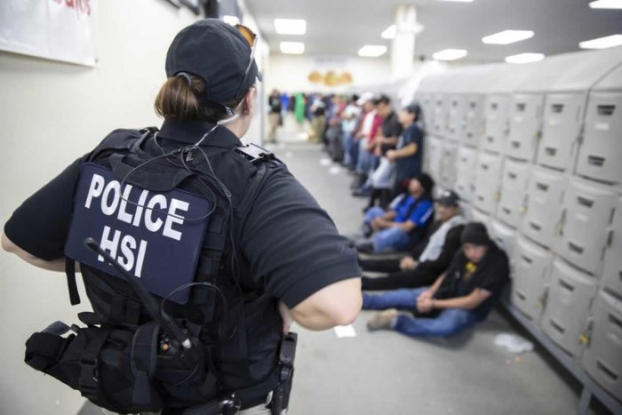 This image released by the US Immigration and Customs Enforcement shows a Homeland Security Investigations officer guarding suspected illegal aliens. Credit: AFP/US Immigration and Customs Enforcement