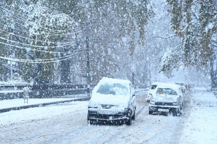Cars covered in snow drive along a road during a first snowfall in Srinagar on November 7, 2019. (AFP)