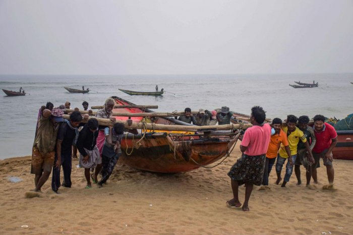 Fishermen pull their boats to away from the sea following Cyclone Bulbul warning, in Puri on Friday. (PTI Photo)