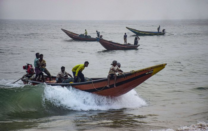Fishermen take their boats to a safe harbour from the sea following Cyclone Bulbul warning, in Puri. (PTI Photo)