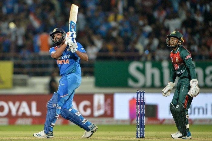 Indian team captain Rohit Sharma (L) plays a shot as Bangladeshi wicketkeeper Mustafizur Rehman looks on during the 2nd T20 International cricket match of three-match series between Bangladesh and India, at the Saurashtra Cricket Association Stadium in Rajkot on November 7, 2019. (Photo by Sajjad HUSSAIN / AFP)