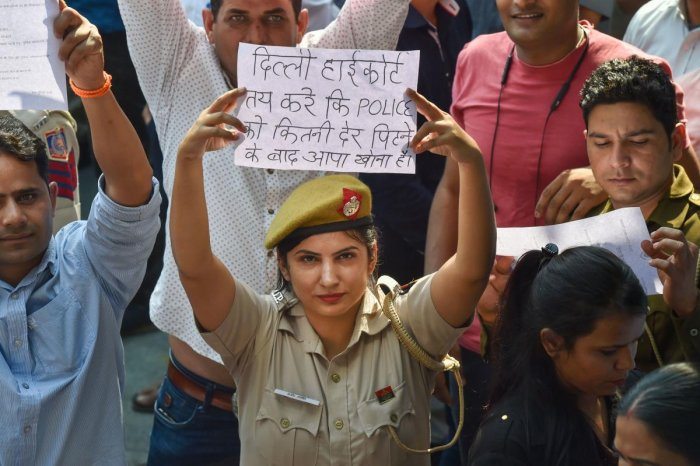 A Delhi Police woman displays a placard during a protest against the alleged repeated incidents of alleged violence against them by lawyers, in New Delhi, Tuesday, Nov. 5, 2019. (PTI Photo)
