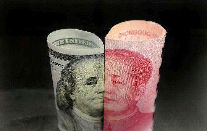 A Benjamin Franklin U.S. 100 dollar banknote and a Chinese 100 yuan banknote with late Chinese Chairman Mao Zedong. (REUTERS/Jason Lee/File Photo)