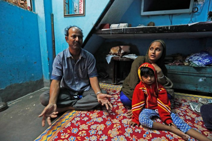 Fareeda and her husband Abdul Hanif sit with their four-year-old daughter inside their house in New Delhi, India. ( REUTERS/Adnan Abidi)