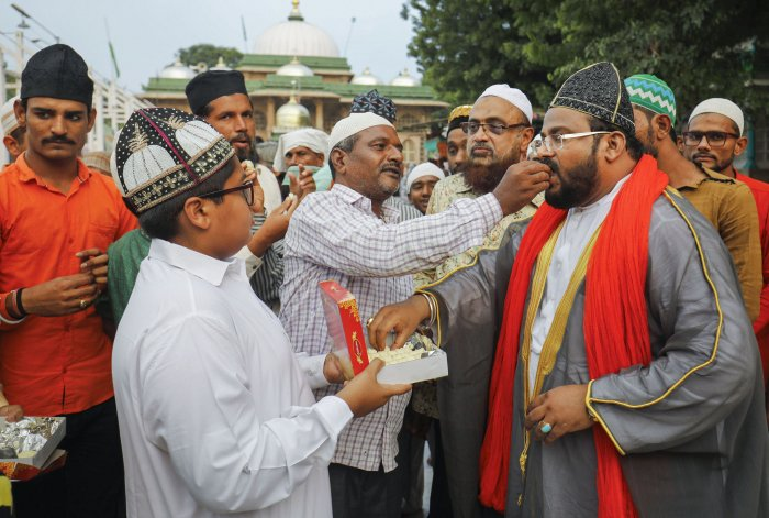 Muslims offer sweets to each other after Supreme Court's verdict outside the Shah-e-alam shrine in Ahmedabad, India, Saturday, Nov. 9, 2019. The apex court on Saturday cleared the way for the construction of a Ram Temple at the disputed site at Ayodhya, and directed the Centre to allot a 5-acre plot to the Sunni Waqf Board for building a mosque. (PTI Photo)