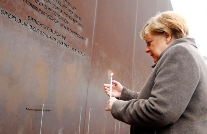 German Chancellor Angela Merkel lights a candle at the memorial of the divided city and the victims of communist tyranny during a ceremony marking the 30th anniversary of the fall of the Berlin Wall at the Wall memorial on Bernauer Strasse in Berlin, Germ