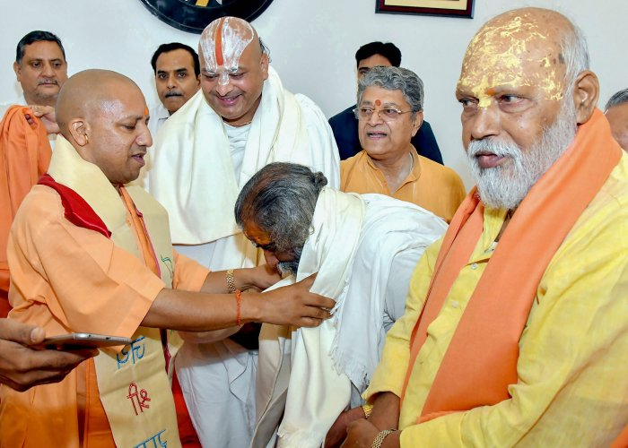 Uttar Pradesh Chief Minister Yogi Adityanath meets a delegation of sadhus and saints during a meeting over early construction of Ram Temple at Ayodhya, in Lucknow on Thursday. PTI