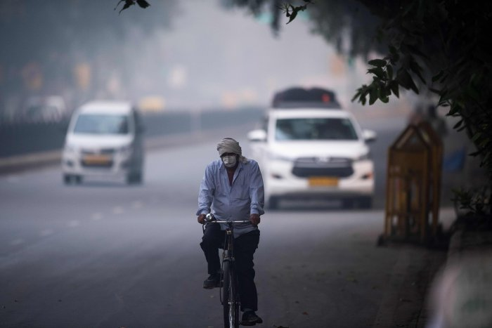A man wearing protective face mask rides a bicycle along a street in smoggy conditions in New Delhi. (AFP Photo)