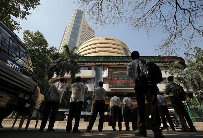 People look at a screen displaying the Sensex results.(REUTERS)