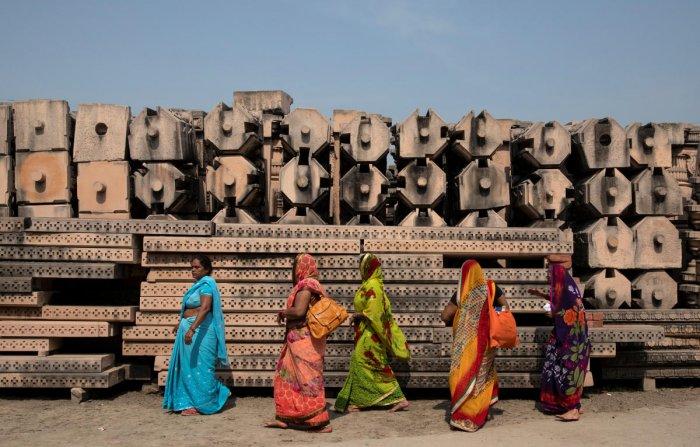 Devotees walk past the pillars that Vishwa Hindu Parishad (VHP) say will be used to build a Ram temple in Ayodhya. Reuters file photo