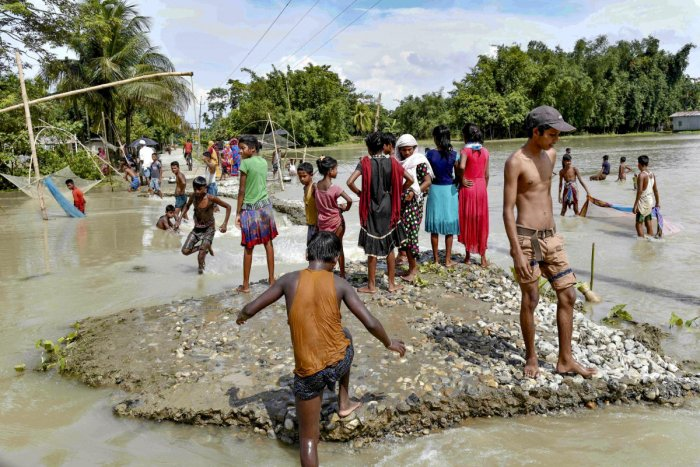 People walk through a flooded area after the Pahumara river overflowed, following heavy monsoon rain, in Barpeta district of Assam (PTI Photo)