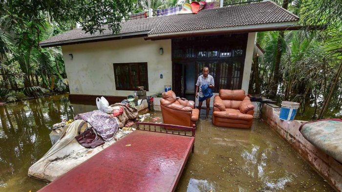 A man cleans up his house after flood water subsided, in Puthenvelikkara near Kochi. PTI photo